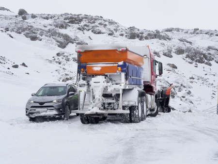 car rescued by a snowplow, Iceland mountain road in winter Reklamní fotografie
