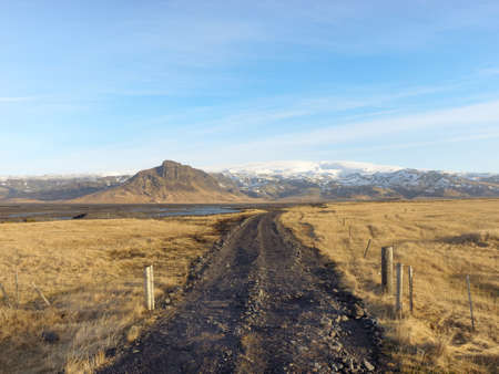dirt road to Klifandi river and Myrdalsjokull glacier with fields in the foreground, south Iceland in winter
