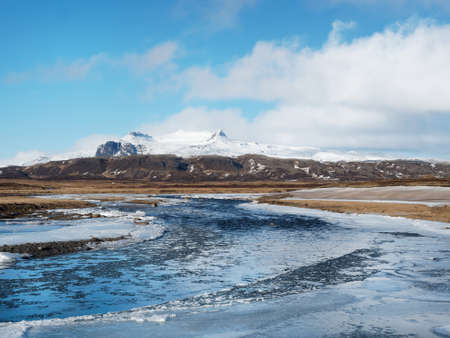 Straumfjardara river with snow covered Ellidatindar mountain peak in the background, Iceland in winter
