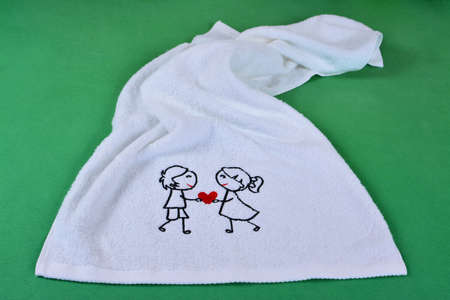 Happy Valentines day, white towel on the green background. 스톡 콘텐츠