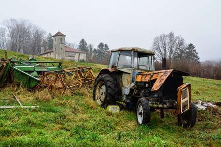 alter Traktor auf dem Feld, nebliger Morgen Standard-Bild