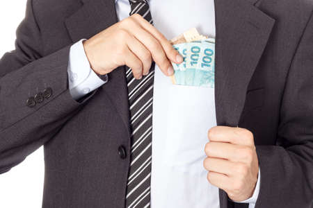 putting money in pocket: A businessman in a suit putting money in his pocket isolated on white background
