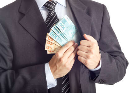 venality: A businessman in a suit putting money in his pocket isolated on white background