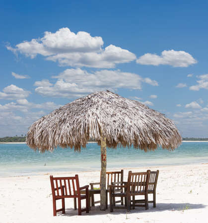 thatched: beach chairs under the shade of a palapa sun roof umbrella in Jericoacoara, Brazil