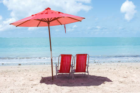 red umbrella: Pair of chairs and an umbrella on the beach of Ponta Verde, Maceio, Alagoas, northeast of Brazil