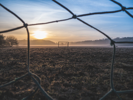 Beautiful foggy soccer pitch on a field at sunrise Stock Photo
