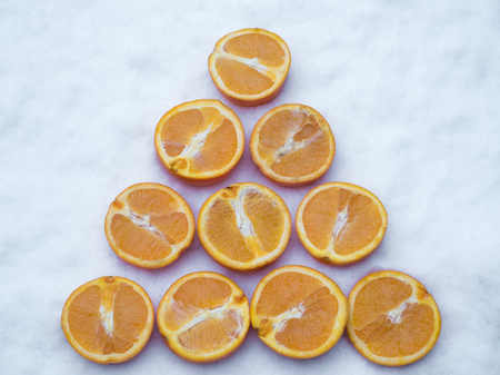 Orange slices rowed up in the snow, top view shot Stock Photo