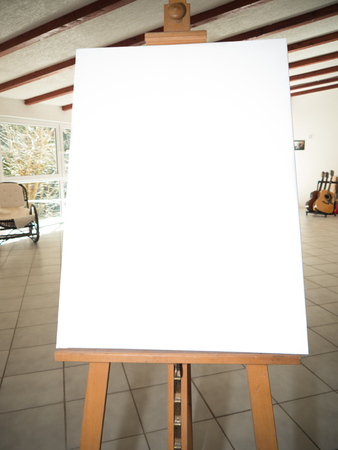 artist's canvas: white canvas on a wooden easel in a studio with guitars and a piano