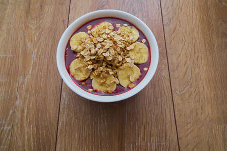 Top view of Brazilian açaí bowl with bananas and Granola with copy space Stock Photo