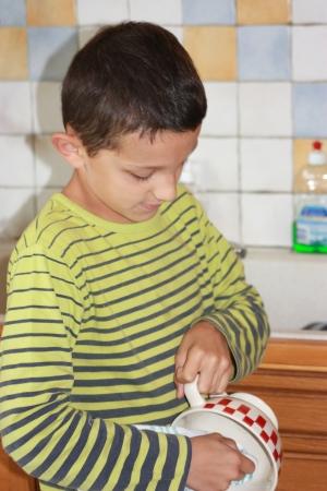 niño limpiando los platos photo