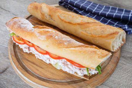 tuna sandwich and raw vegetables on a cutting board