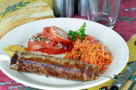 grilled andouillette and raw vegetables in a plate