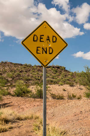 dead end: DEAD END Road Sign with Bullet Holes and Peeling Letters in Arizona Desert
