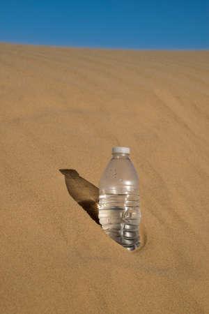 dehydration: Water Bottle Buried in Sand in the Desert