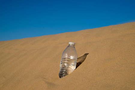 sediento: Botella de agua estancada en la arena del desierto