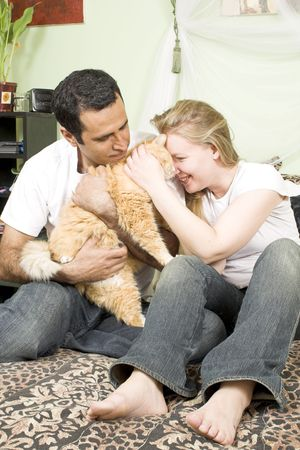 happyness: loving couple with cat in bed Stock Photo