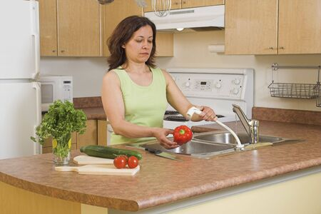 mujer lavando verduras Foto de archivo - 407549
