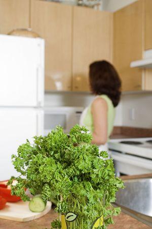 woman opening the fridge - focus on parsley photo