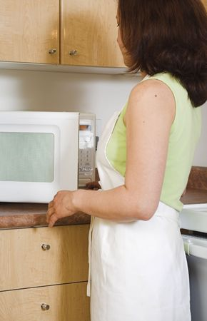 woman opening the microwave photo