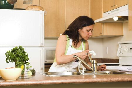 woman in kitchen using sink photo