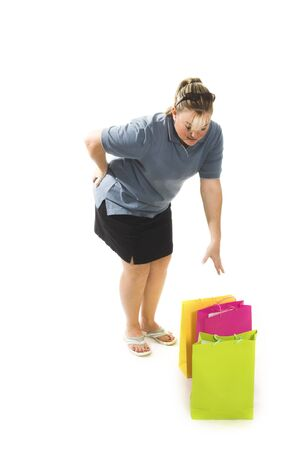 woman with back pain picking up bags