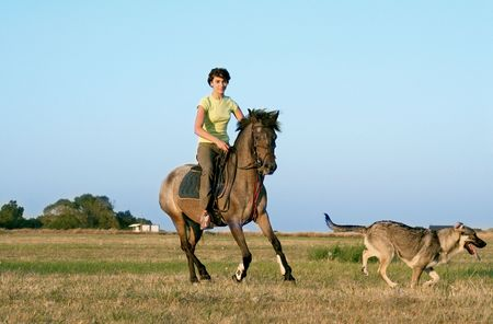 teen riding horse with dog photo