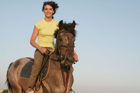 teen riding horse with yellow shirt Stock Photo
