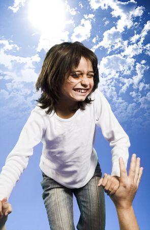 little girl jumping high over blue sky