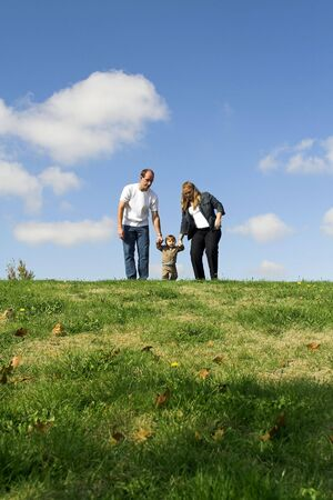 family walking on field over blue sky Stock Photo - 554105