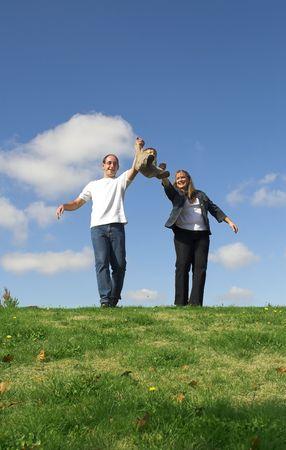 happy family making boy jump over blue sky Banco de Imagens