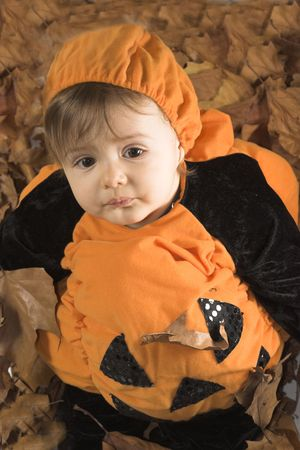 baby dressed in halloween disguise sitting on leaves