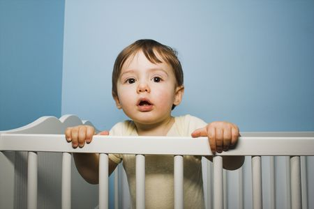 standing in his crib over blue wall Stock Photo