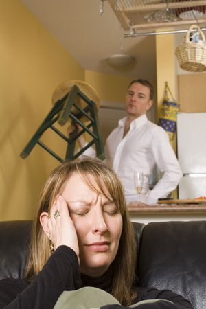 couple arguing in apartment with sad and angry expressions Stock Photo