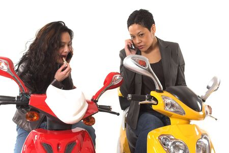 couple girls talking on cell phone and doing make up over white background photo