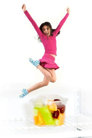 teen jumping over fruit cup over a white background 스톡 콘텐츠
