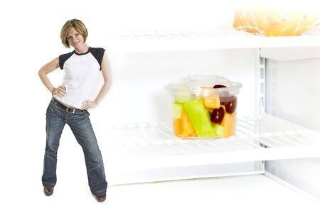 calories poor: woman standing beside fruit cup in fridge