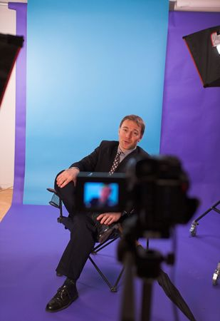 businessman being videotapped in studio over blue background