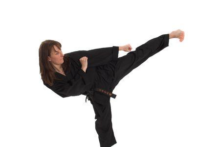 female kick: woman doing karate over white background Stock Photo
