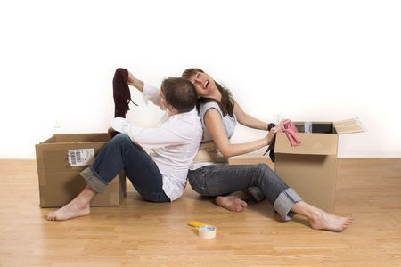 happy couple moving in new apartment opening boxes Stock Photo
