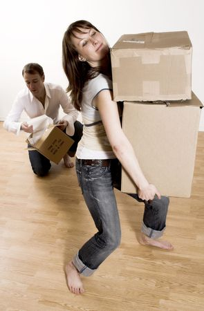 appartment: couple moving in appartment - woman carrying all boxes