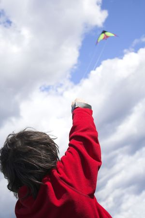 day time: teen flying kite at day time taken from behing