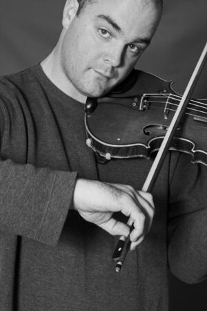 portrait of man playing violon in black and white