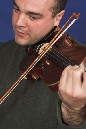 portrait of man playing violon over blue background