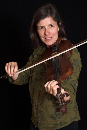 mid-age woman playing violon over black background