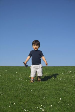 tranquille: child standing in field over deep blue sky