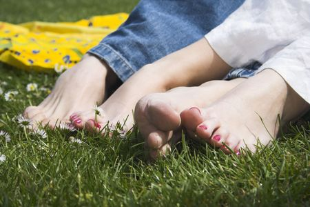 couple showing their feet on grass with flowers 免版税图像