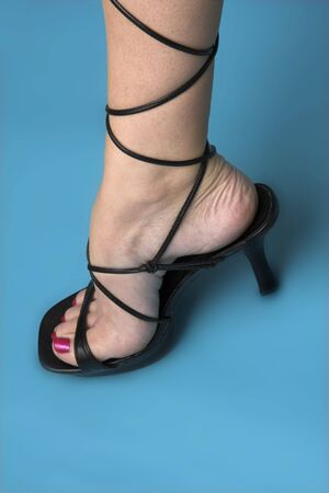 sexy feet: portrait of foot in high heel over blue background