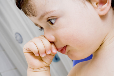 baby boy with itchy nose  in the bathroom Stock Photo