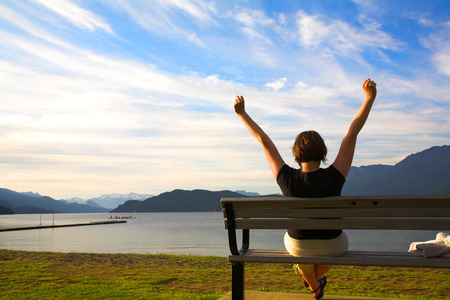 woman with her arms up over blue sky