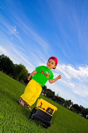 child playing with truck outside over deep blue sky photo